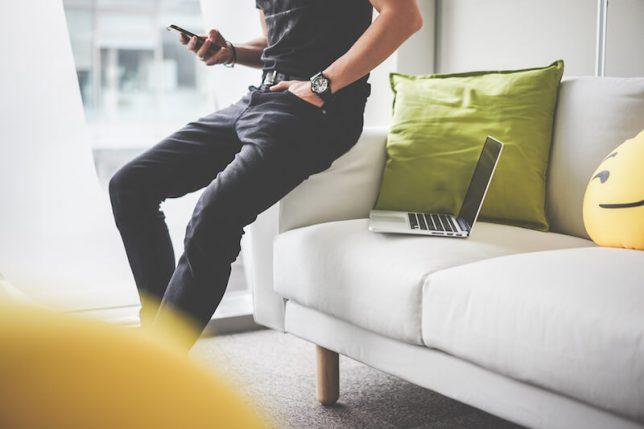 暇つぶしにスマートフォンを見ている男性の画像