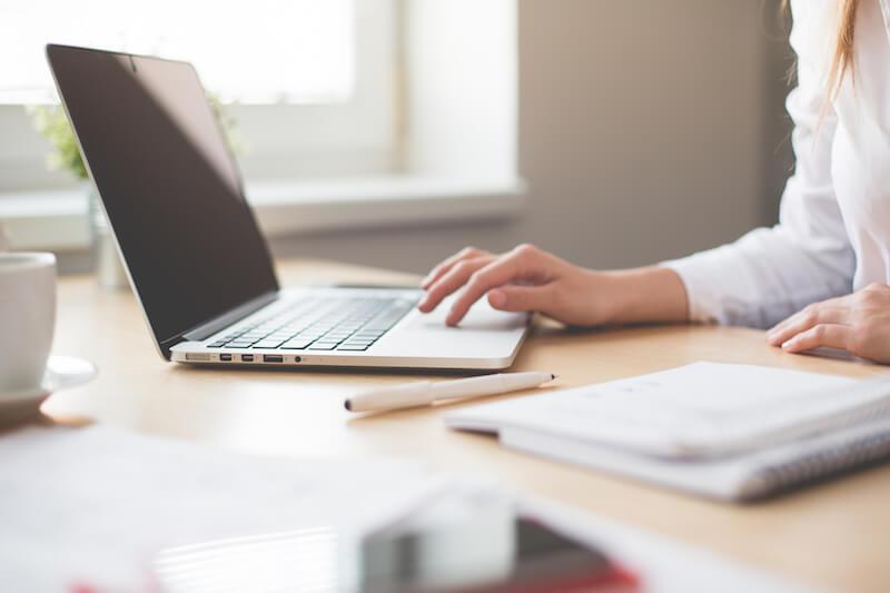 女性が使用を見ながら事務作業をしている画像