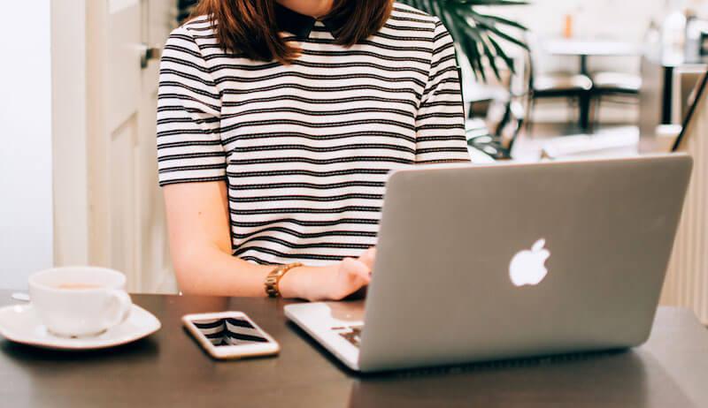 iPhone・MacBookを使ってブログを運営する女性の画像