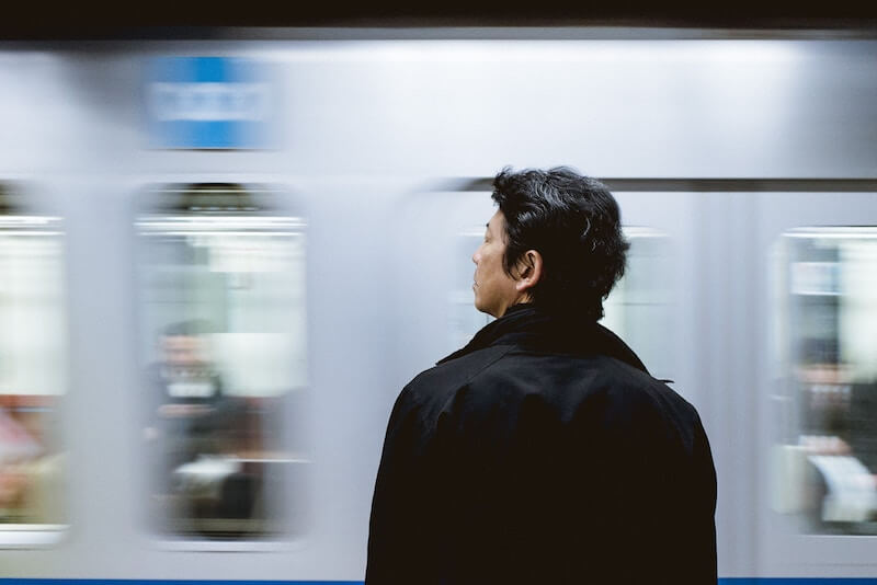 疲れ切った顔で電車を見る男性の画像