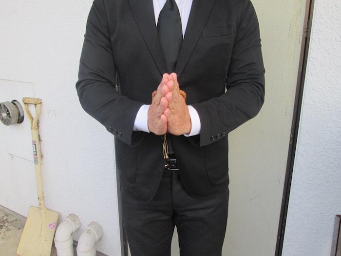 斎場の入り口で合掌している男性の画像