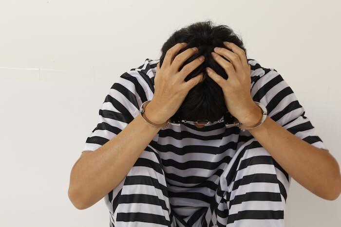 逮捕されて頭を抱えている男性の画像