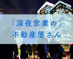 深夜に高層マンションの前を歩いている会社員の画像