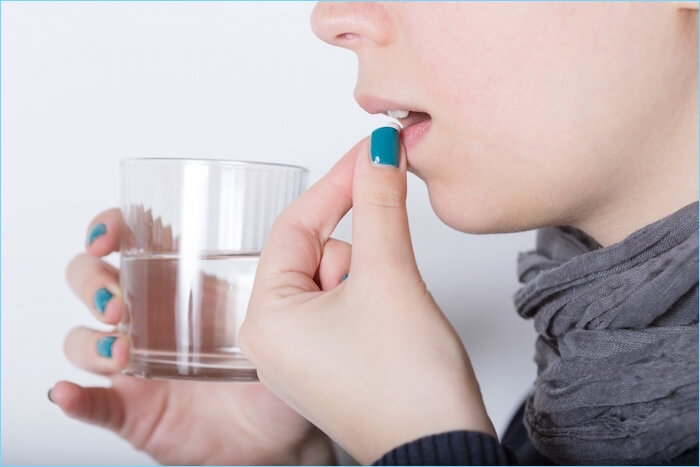 錠剤を飲もうとしている女性の画像